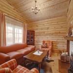 Интерьер маленькой гостиной с камином в деревянном доме