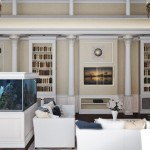 Фото интерьера большой гостиной с аквариумом и двумя люстрами в частном доме
